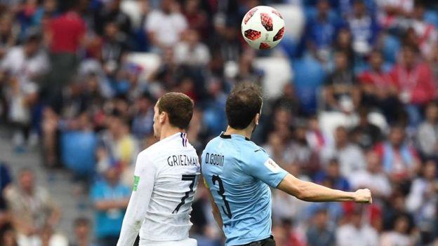 Antoine Griezmann disputa un balón con Diego Godín