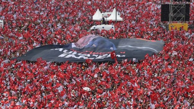 Thousands of supporters wave flags and cheer as they listen during an election rally for Muharrem Ince