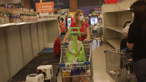 Una mujer en Chile pasea por los estantes vacíos de un supermercado