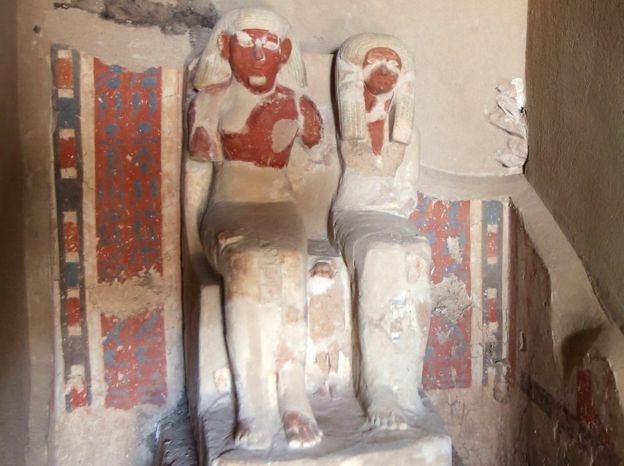 A carved sandstone statue depicting the tomb's owner Amenemhat sitting on a high back chair beside his wife at a recently discovered tomb in the Draa Abul Nagaa necropolis, Luxor's West Bank, 700km south of Cairo,