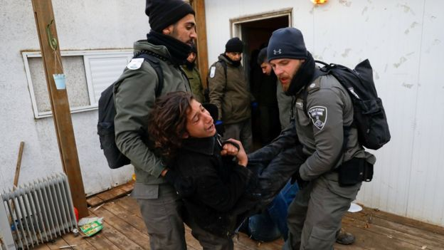 Israeli policemen remove a pro-settlement activist from a house during an operation to evict settlers from the unauthorised outpost of Amona in the occupied West Bank (1 February 2017)