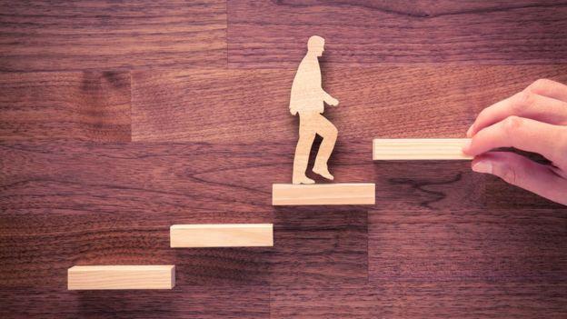 Hombre de madera asciende en escalones.