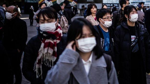 Tokyo'da hastalıklarını başkalarına geçirmemek için maske takan insanlar.