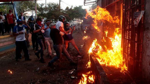 Manifestantes antigubernamentales celebran la quema de Radio Ya, en Managua.
