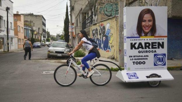 Una joven arrastra un anuncio político en una bicicleta
