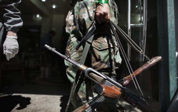 A Syrian rebel holds AK-47 rifles belonging to wounded comrades