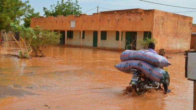 Мотоциклист со своими пожитками едет по затопленной улице Ниамейя