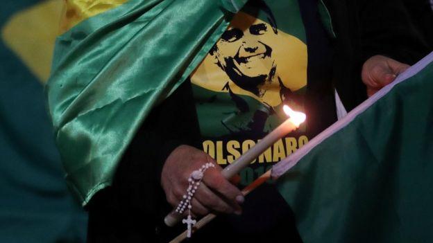 Uma mulher acende uma vela para o candidato presidencial Jair Bolsonaro depois que ele foi esfaqueado em 6 de setembro de 2018