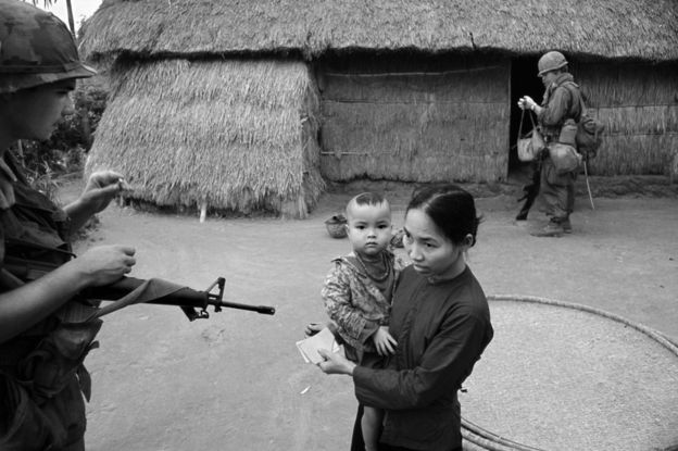 A soldier pointing a gun at a mother and child