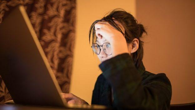 Mulher jovem usando laptop durante a noite, seu rosto iluminado pela luz da tela