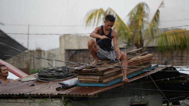 Un filipino en Tuguegarao, capital de Cagayan, reforzando su casa ante la llegada el tifón Mangkhut.