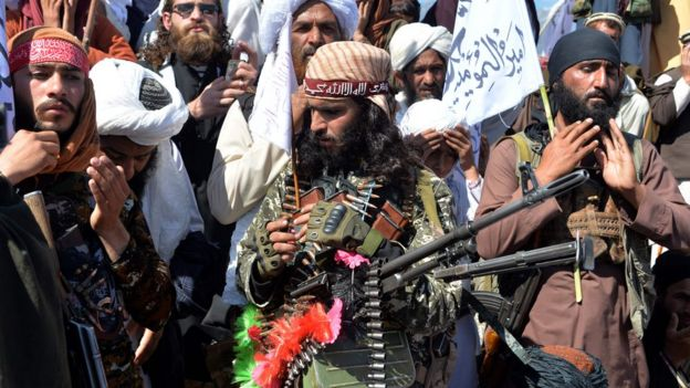 Afghan Taliban militants and villagers attend a gathering