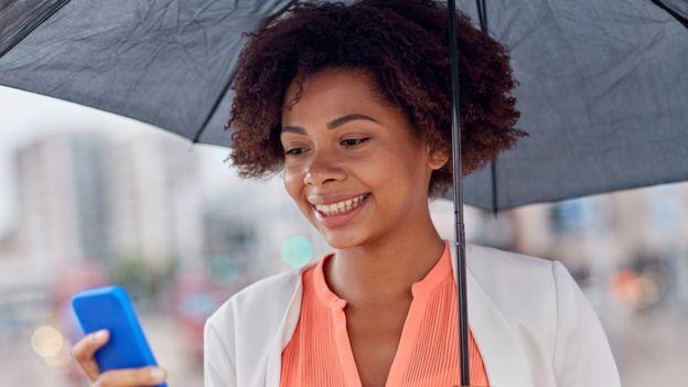 Mujer usando celular en la calle