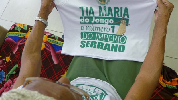 Tia Maria segurando a camiseta do Império Serrano que diz que ela é a número 1 da escola