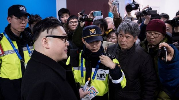 A Kim Jong-un impersonator is surrounded by journalists who try to film him on their cameras and phones