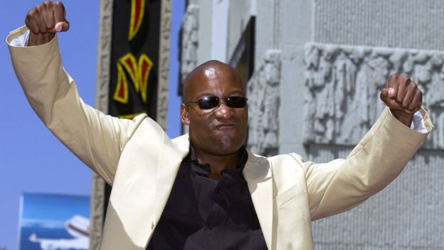 John Singleton poses with arms in the air