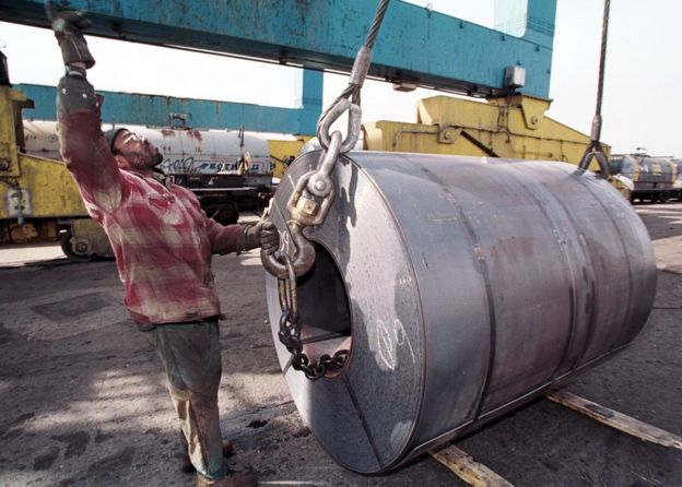 An employee of the South Jersey Port Corporation in Camden NJ with a coil of imported steel