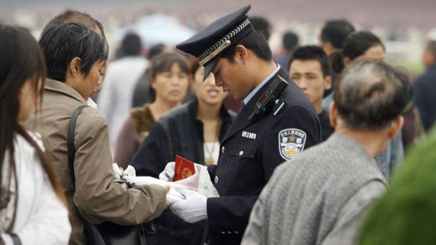Un policía revisa la identificación de un ciudadano.