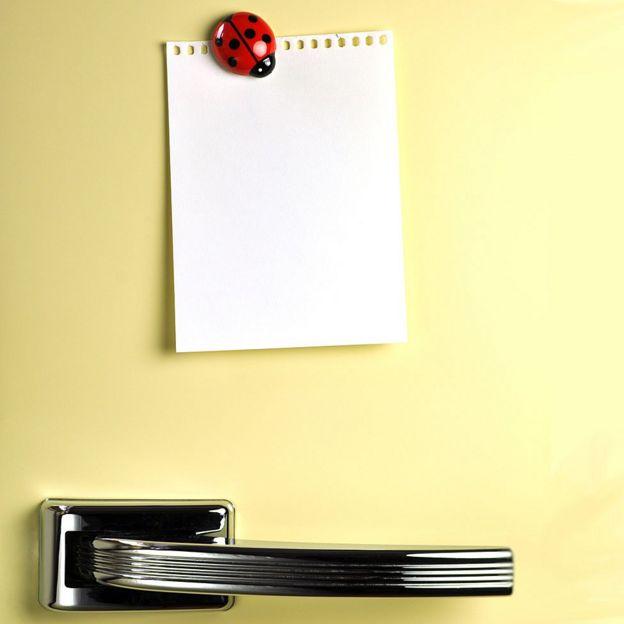 Puerta de nevera con imán sosteniendo un papel.