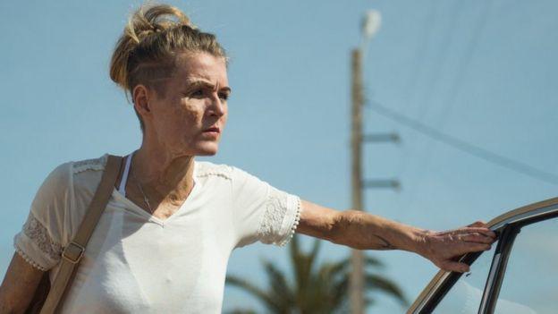 Vicky Knight posa en la película, apoyada en la puerta de un auto.