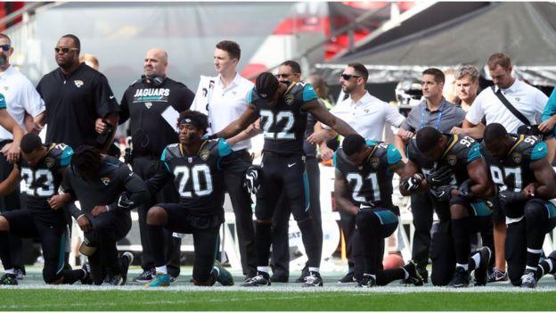 Члены команды Jacksonville Jaguars преклоняют колена в знак протеста во время исполнения американского гимна на стадионе Уэмбли в Лондоне