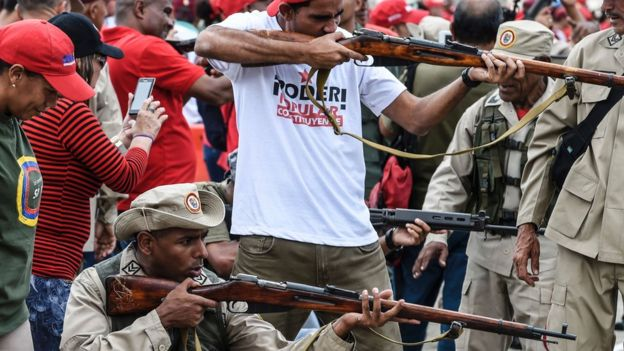 Civiles sin uniformes y milicianos disparando.