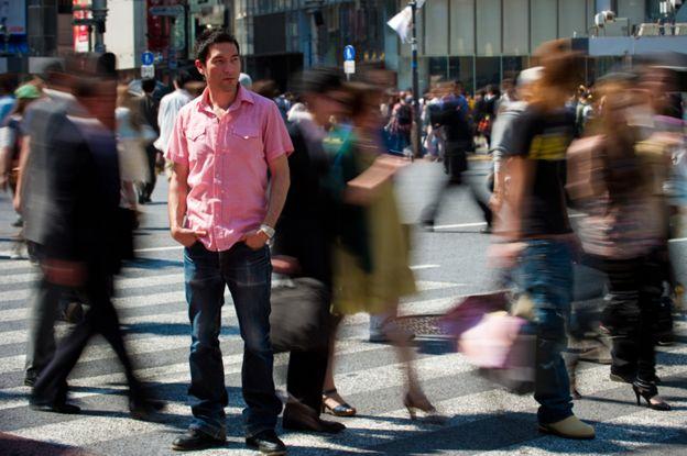 Un hombre solo en una ciudad llena de gente.