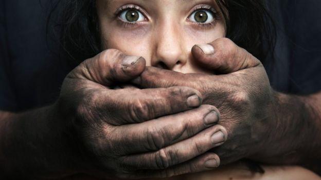 Foto ilustrativa sobre abuso infantil - homem segura com as duas mãos rosto de menina