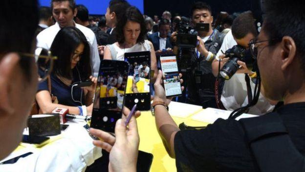Pessoas testando celulares em feira de tecnologia