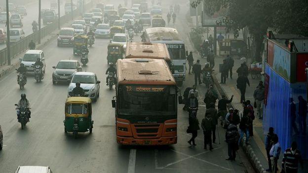 Buses y autos en una calle india con el aire contaminado