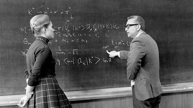 Gell-Mann discutiendo frente a un pizarrón con la física estadounidense Mary Katharine Gaillard en 1972