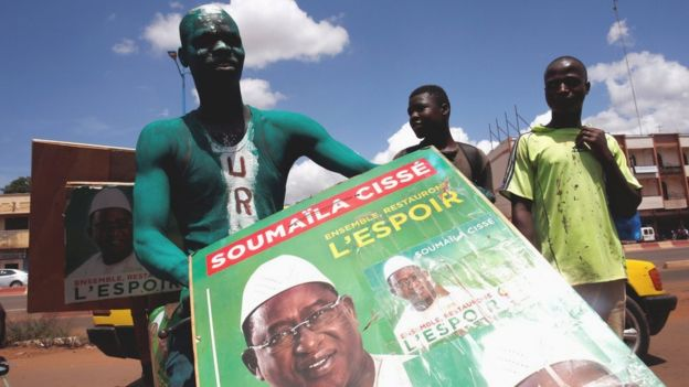A supporter of presidential candidate Soumaila Cisse holding a campaign poster