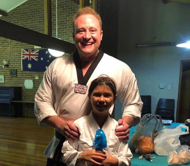 Charles con su hija y vestidos con uniformes de artes marciales.