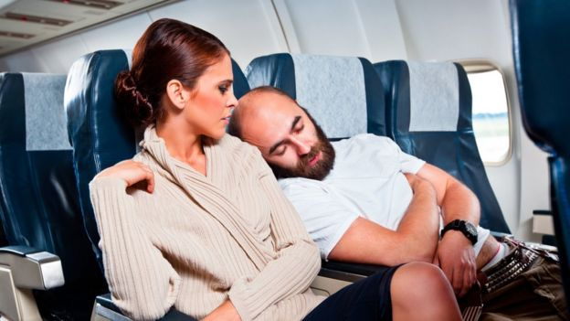 Un hombre se recarga en el hombro de una mujer en un avión