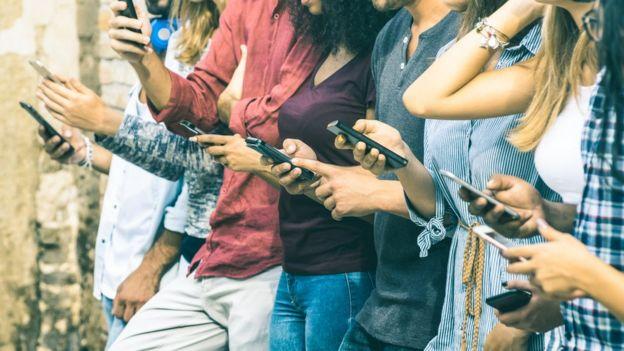 Personas jóvenes consultando sus teléfonos inteligentes