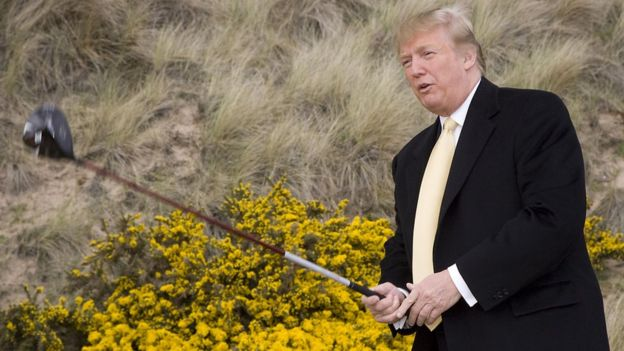 Trump com um taco de golfe