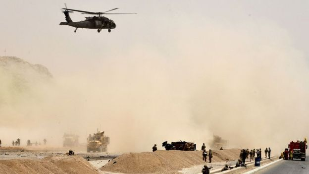 Un helicóptero negro de Estados Unidos vuela sobre el sitio de un ataque suicida talibán en Kandahar.