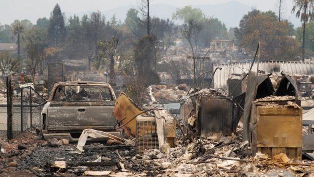 Automóvil y estructuras quemadas por el incendio Carr en California.