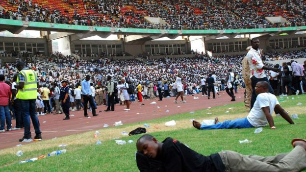 Job-seekers lie on the pitch after a stampede in Abuja National Stadium, where thousands of job-seekers came to apply for work at the Nigerian immigration department, in Abuja, on March 15, 2014