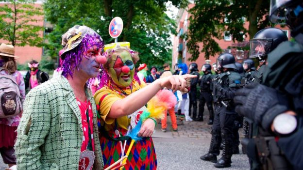 Demonstrators dressed as clowns face policemen as they take part in a protest titled