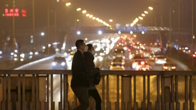 People wearing protective masks on an overpass during the evening rush hour amid the heavy smog in Beijing, 7 Dec