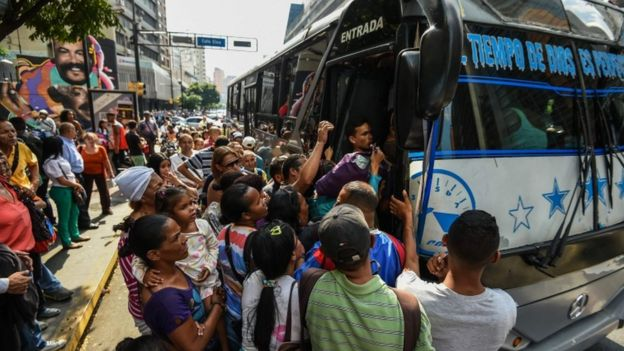 A crowded bus in Caracas with a huge queue outside