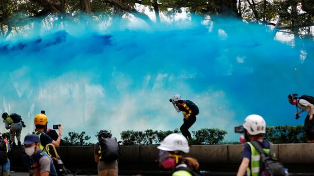 A wave of surreal blue water streaking through the air as journalists and protesters duck to avoid the dye in an open space