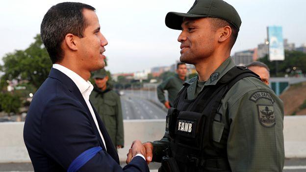 Juan Guaidó, com uma fita azul no braço, aperta a mão de um militar