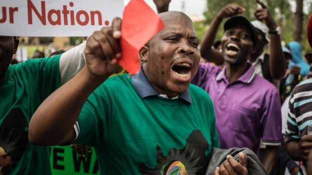 South Africans shout slogans as they take part in a protest for the resignation of South African President Jacob Zuma