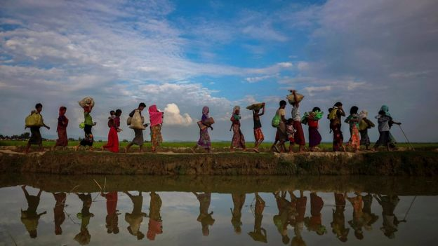 Rohingya refugees walking along a lakeside in Bangladesh