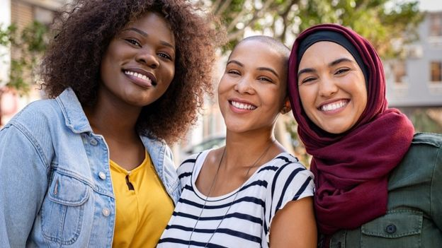 Group of three happy multiethnic friends looking at camera.