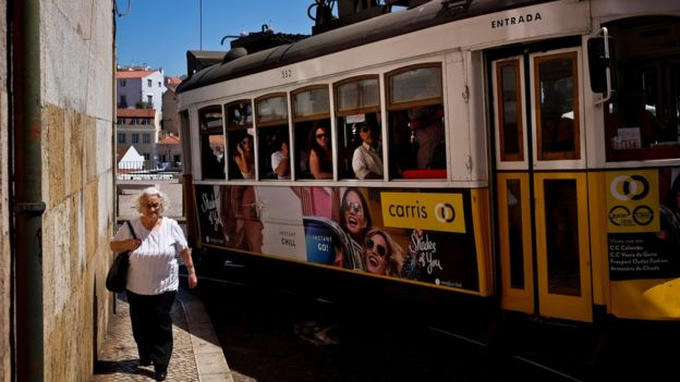 Una mujer pasea por Lisboa ante un tranvía.