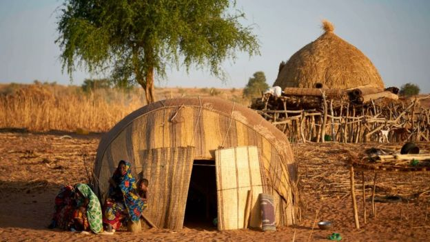 A family sits in front of their home in the Soum region in northern Burkina Faso
