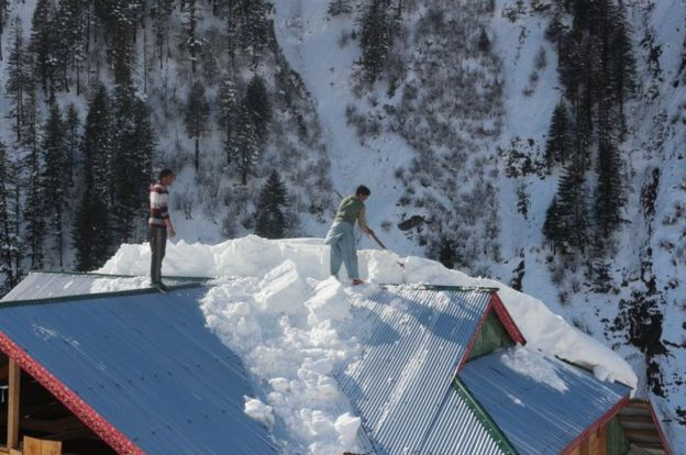 Villagers clear snow from roofs in Neelum valley